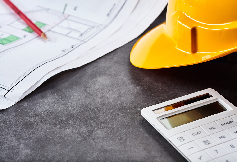 Blueprint plans, pencil, yellow hardhat and calculator