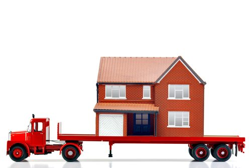 A flatbed articulated lorry loaded with a house isolated on a white background.
